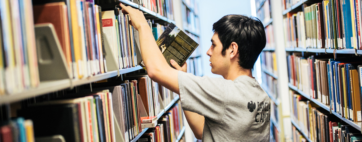Image of a student browsing the book stacks at the William H. Hannon Library.