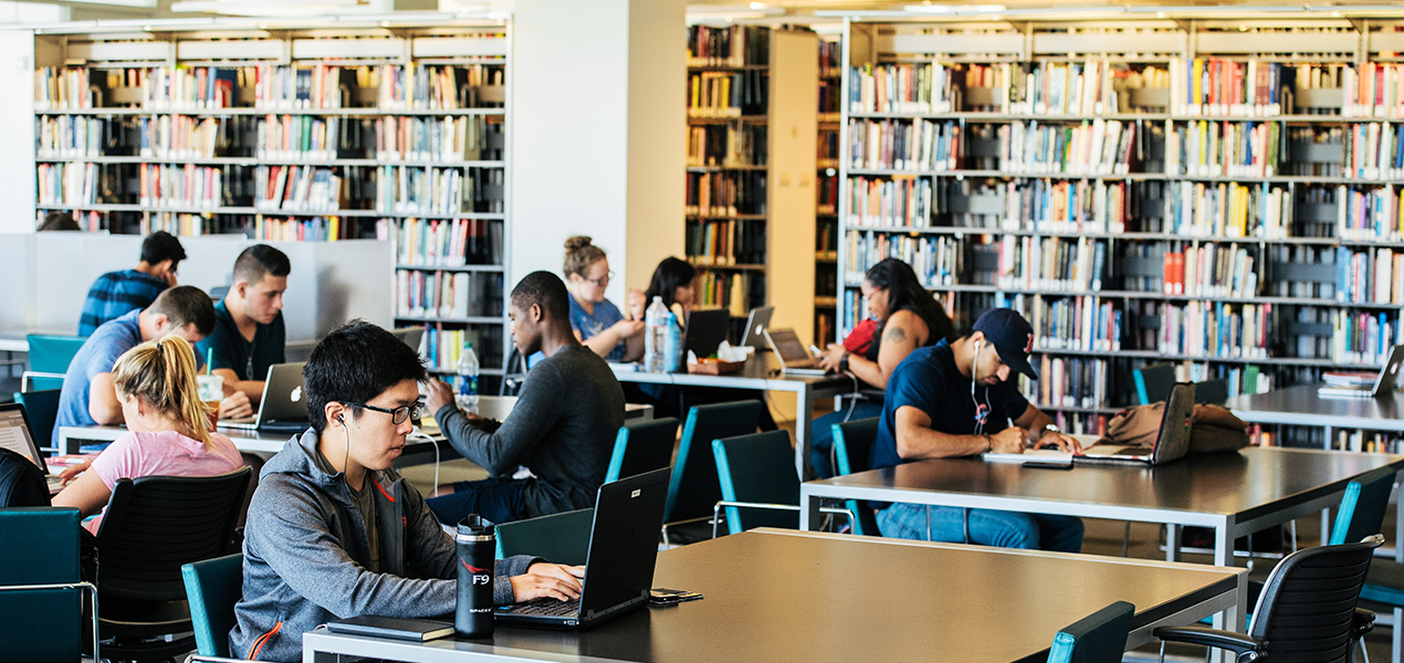 Students sitting at different tables and studying in the library.